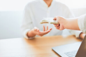 Close-up of hands giving dollar pay compensation from work. Give rewards as incentives for work, on office desk background.
